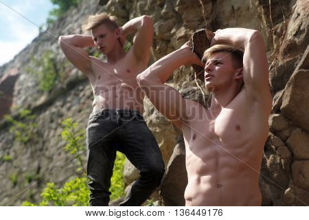Muscular young twins with beautiful sexy body and bare torso standing sunny day near mountain rocks in pants