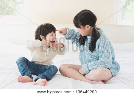 Asian sister and brother quarreling on white bed