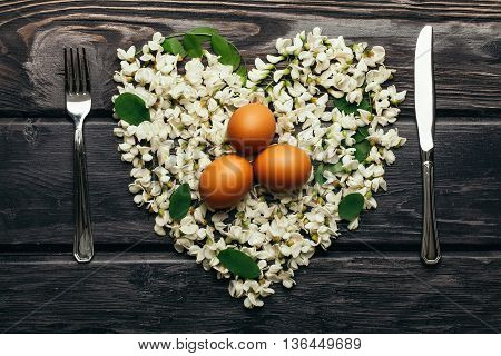 Three eggs on white acacia blossoming flower petals arranged in heart shape with fork and knife on dark wooden background