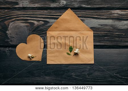 Envelope open and empty heart note of brown paper with acacia petals on dark wooden background