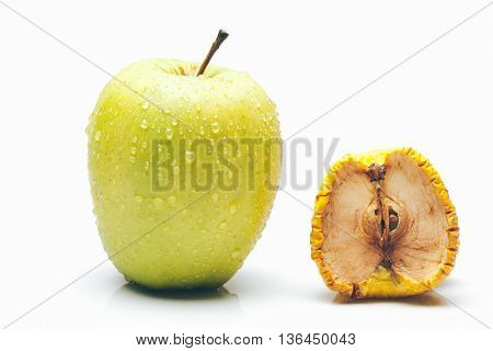 fresh green apple with water drops compared with dried and wrinkled pieces with seeds isolated on white background time or aging concept