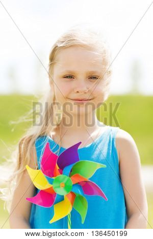 summer, childhood, leisure and people concept - happy little girl with colorful pinwheel toy outdoors