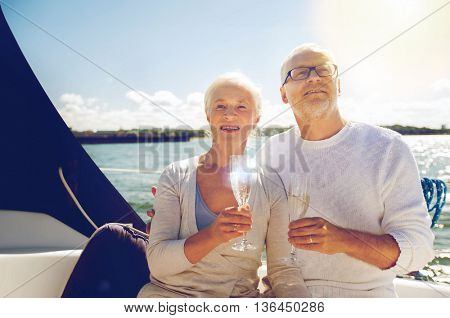 sailing, age, travel, holidays and people concept - happy senior couple with champagne glasses on sail boat or yacht deck floating in sea