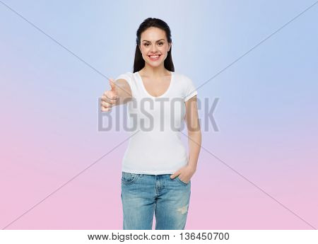 advertisement, gesture, clothing and people concept - happy smiling young woman or teenage girl in white t-shirt showing thumbs up over rose quartz and serenity gradient background