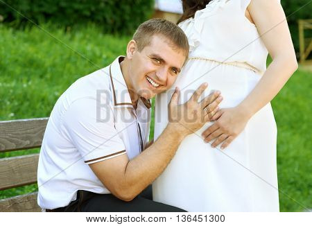 pregnant woman and husband, man listen belly and talk with baby, happy family, couple in city park, summer season, green grass and trees