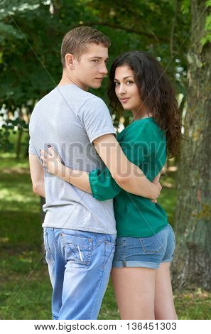 Romantic couple posing in city park, summer season, young people backside