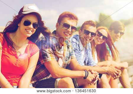 friendship, leisure, summer and people concept - close up of smiling friends sitting on city street