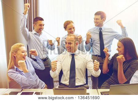 business, people, technology, gesture and teamwork concept - smiling business team raising hands and celebrating victory in office