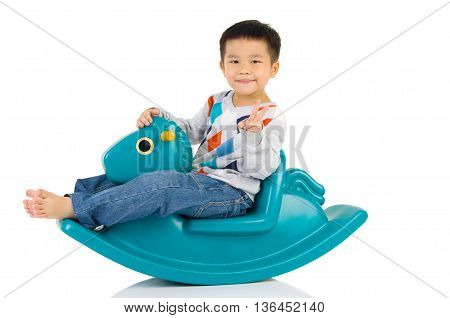 smiling asian boy playing with Toy horse