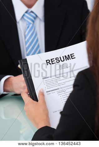 image of female candidate holding resume at desk during interview