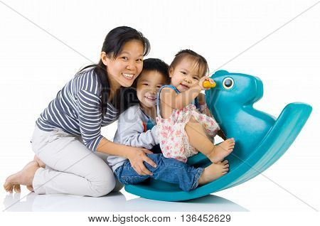 smiling asian family playing with Toy horse