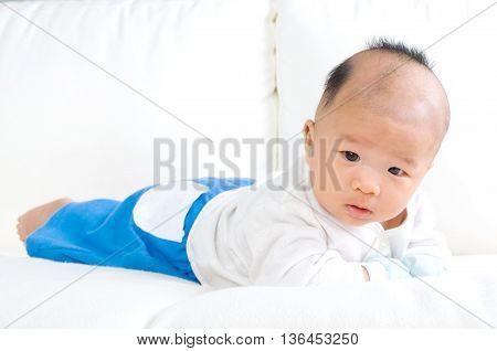 crawling beautiful asian baby boy on sofa