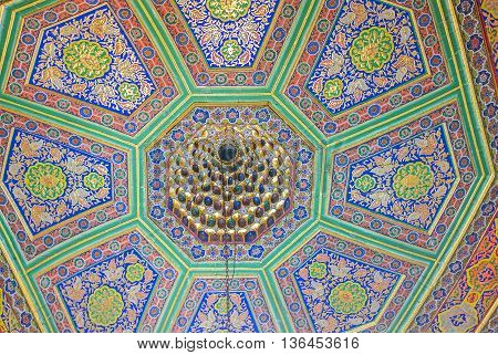 BUKHARA UZBEKISTAN - APRIL 29 2015: The complex carving and colorful floral paintings on ceiling in the Museum of Costume of Sitorai Mokhi-Khosa Complex on April 29 in Bukhara.