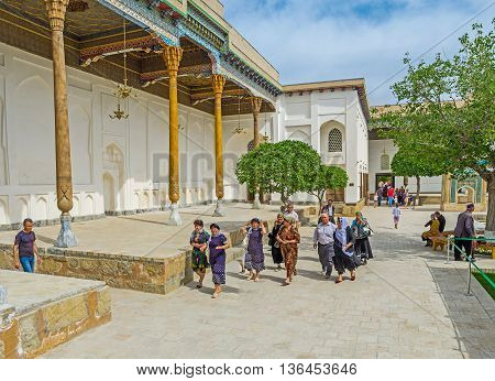 BUKHARA UZBEKISTAN - APRIL 29 2015: The group of pilgrims in the courtyard of Sheikh Naqshband Mausoleum on April 29 in Bukhara.