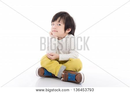 Cute asian child sitting and looking on white background isolated