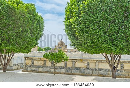 The old cemetery of Bahauddin Nakshband Memorial Complex surrounded by the lush green trees Bukhara Uzbekistan.