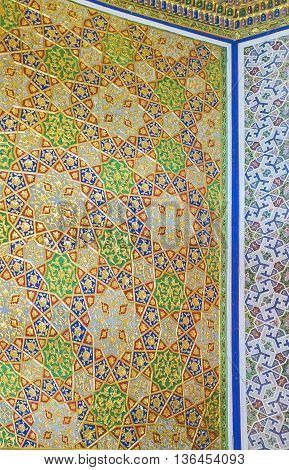 BUKHARA UZBEKISTAN - APRIL 29 2015: The colorful stars on the golden background on the wall of the Museum of Costume of Sitorai Mokhi-Khosa Complex on April 29 in Bukhara.