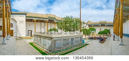 BUKHARA UZBEKISTAN - APRIL 29 2015: Panorama of Sheikh Naqshband Mausoleum with the stone sarcophagus surrounded by the richly decorated gallery with carved wooden pillars and painted ceiling on April 29 in Bukhara.