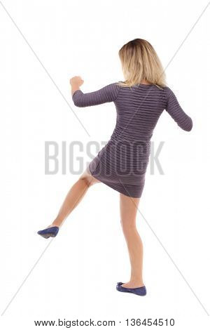 skinny woman funny fights waving his arms and legs. Isolated over white background. Blonde in a short dress strikes the right foot.
