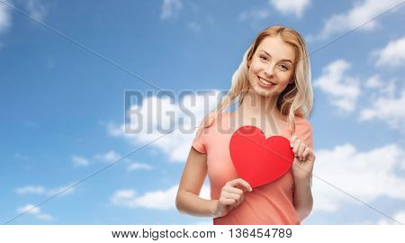 love, romance, charity, valentines day and people concept - smiling young woman or teenage girl with blank red heart shape over blue sky and clouds background