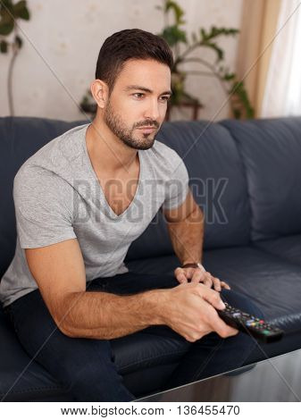 Man switching TV channels by remote control at home