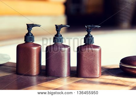 beauty, body care, luxury and hygiene concept - close up of liquid soap or body lotion set at hotel bathroom
