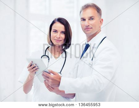 healthcare and technology concept - two doctors looking at tablet pc