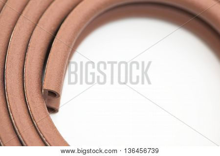 Closeup of roll of brown multipurpose sticking bumper over white background