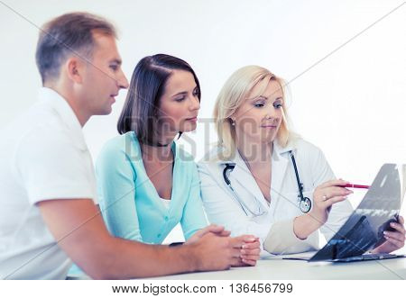 healthcare and medical concept - doctor with patients looking at x-ray