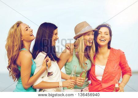 summer holidays and vacation concept - smiling girls with drinks on the beach