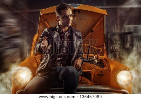 Smart driver is sitting on his old car in the garage and pointing on you.