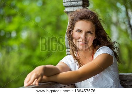 Portrait of young smilin woman in the summer park