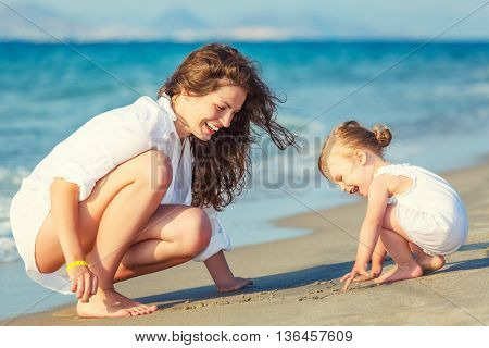 Mother and daughter playing on the beach