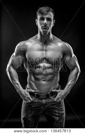 Muscular bodybuilder guy doing posing over black background. Naked torso in jeans. He looks into the camera. Black and white, b w