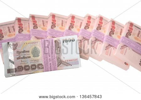 Pack of 100 banknotes of 1000 baht in front of packs of 100 of new banknotes of 100 baht isolated on white background
