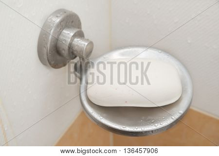 Closeup of stainless steel soap dish inside bathroom with a lot of water drop