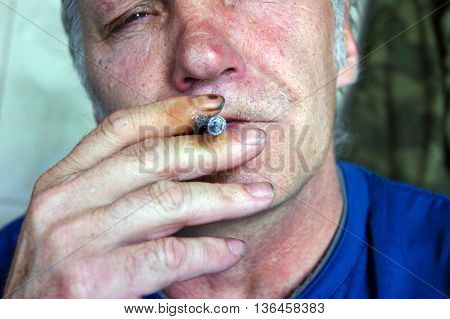 The Person old men with cigarette.Cigarette in mouth