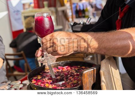 Refreshing sangria with fruits being served on urban street food stall. Urban international kitchen event in Ljubljana, Slovenia, in summertime.