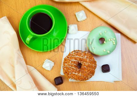 Sweet donuts and cup of black coffee morning light breakfast