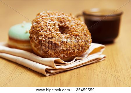 Fresh donut on a napkin and cup of strong coffee