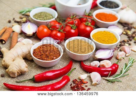 fragrant spices in bowls peppers tomatoes garlic and other cooking ingredients