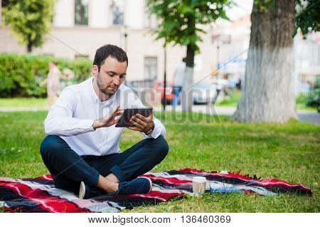 young businessman at the park working with tablet.