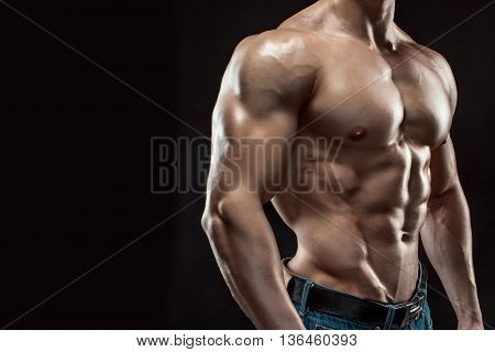 Muscular bodybuilder guy doing posing over black background. Naked torso in jeans. Close-up, free space for text