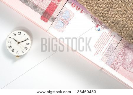 Pack of 100 bank notes of 100 Thai baht inside agriculture sack with clock over white table background. It's represent a concept of farmer life which gain money from specific season only.