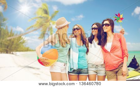 summer holidays, vacation and beach activities concept - smiling girls in shades having fun on the beach