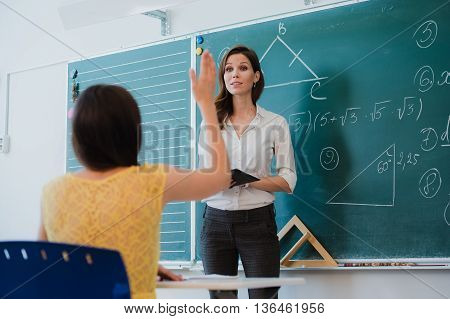 Teacher or docent or educator giving while lesson in front of a blackboard or board a sheet of paper and educate or teaching students or pupils or mates in a school or class.