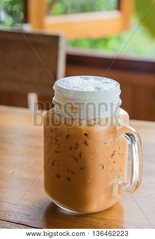 Milk tea with ice in Glass handle on wooden table.Milk glass top.