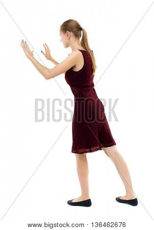 back view of woman pushes wall. Isolated over white background. Rear view people collection. backside view of person. Blonde girl in a burgundy dress leaned on something.