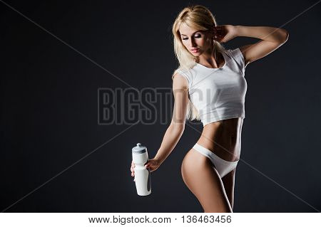 Photo of young woman wearing sportswear with bottle, standing against of dark backround. Studio shot.