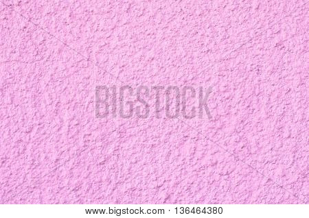 Background of a pink stucco coated and painted exterior rough cast of cement and concrete wall texture decorative coating